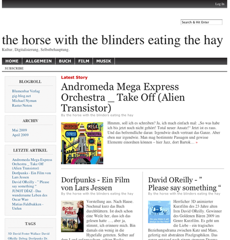 The horse with the blinders eating the hay