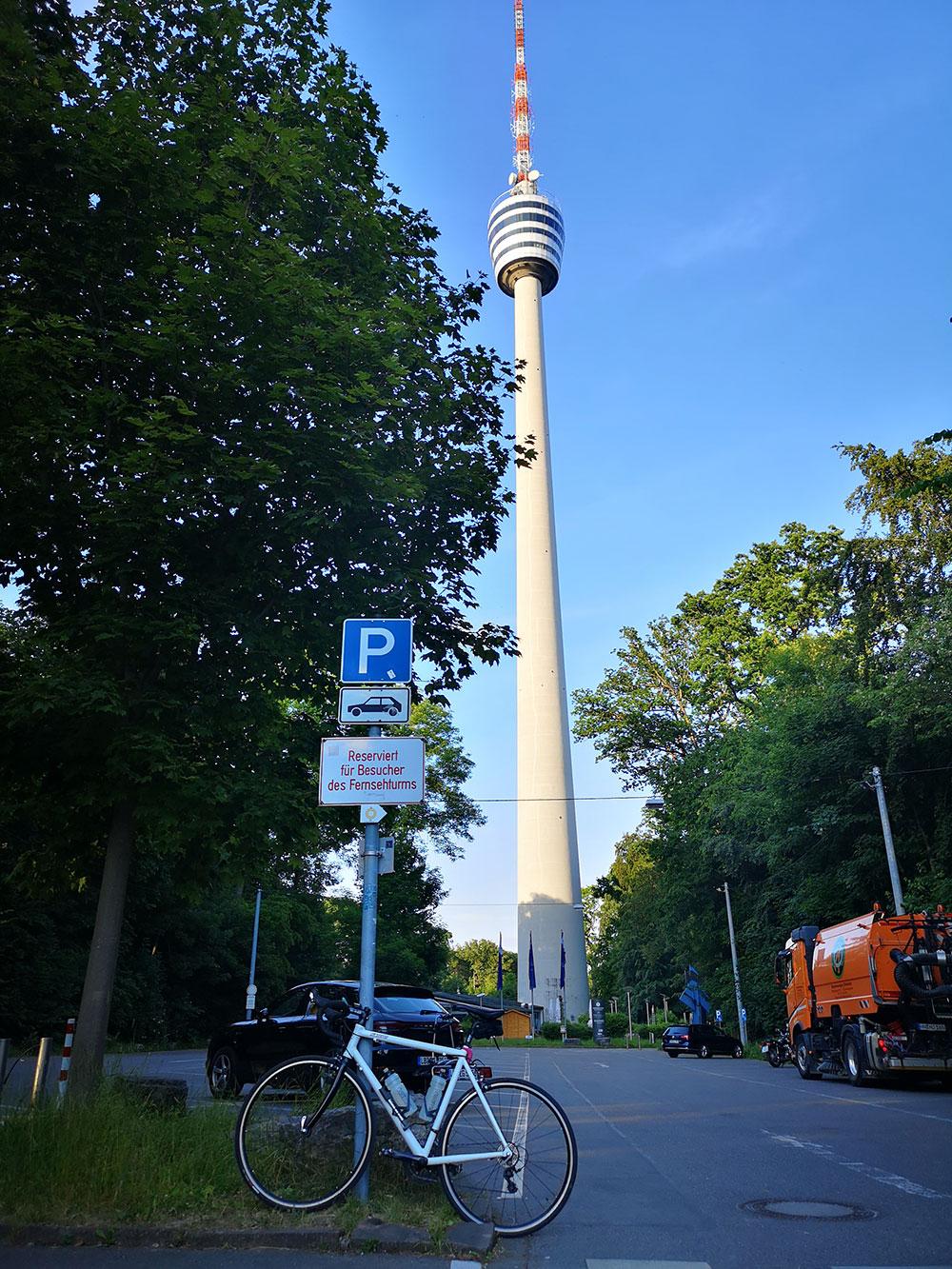 Menners stellen ihr Fahrrad vor einen Turm (Symbolbild).